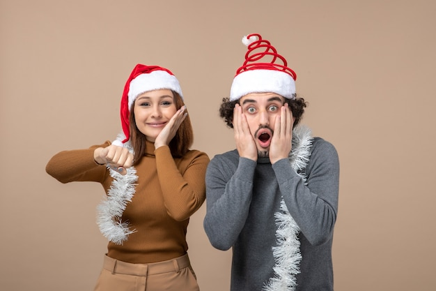 Concept festif de nouvel an humeur avec excité cool couple charmant satisfait portant des chapeaux de père noël rouge se sentir surpris sur gris