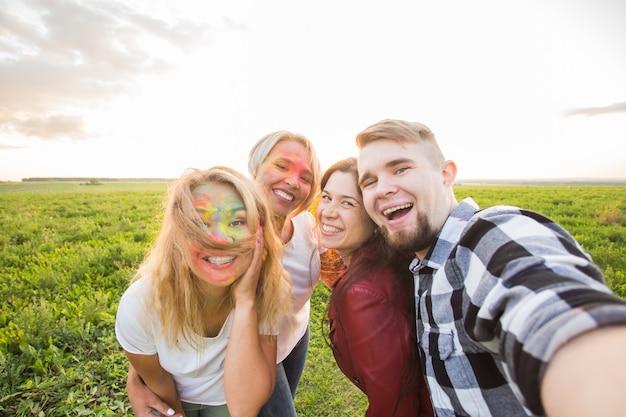 Concept de festival et de technologie - groupe d'amis prenant selfie ou auto photo à l'aide d'un téléphone portable ou