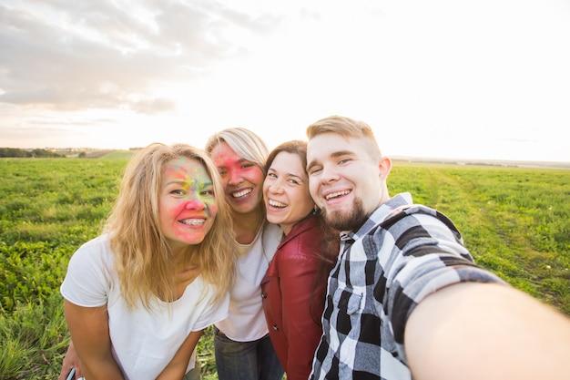 Concept de festival et de technologie - groupe d'amis prenant selfie ou auto photo à l'aide d'un téléphone portable