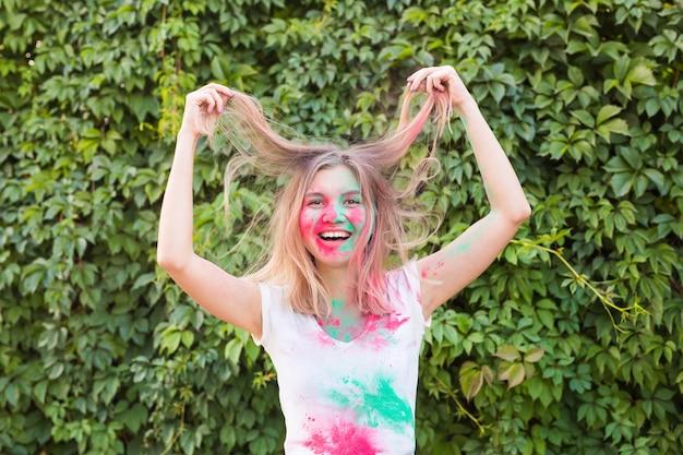 Concept de festival, vacances et personnes holi - jeune femme s'amusant au festival de holi