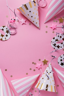 Concept de fête d'anniversaire. chapeaux de fête, masques et bougies d'anniversaire sur fond rose. vue de haut en bas avec espace copie