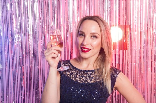 Concept de fête, boissons, vacances et célébration - femme souriante en robe de soirée avec verre de vin mousseux sur mur brillant.