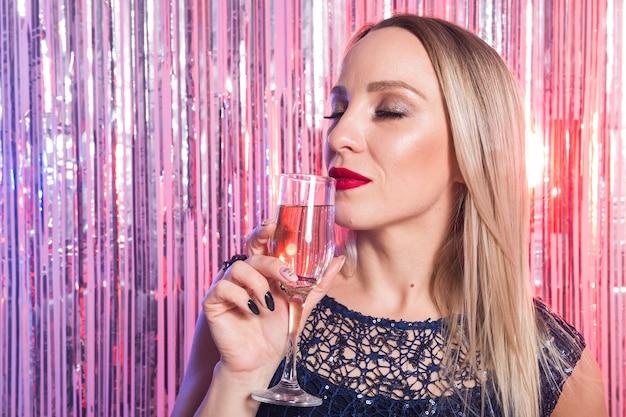 Concept de fête, boissons, vacances et célébration - femme souriante en robe de soirée avec verre de