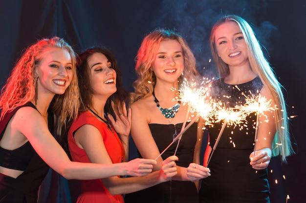 Concept de fête, de célébration et de vacances du nouvel an - jeunes femmes gaies tenant des cierges magiques brûlants.