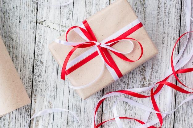 Concept de fête - coffret cadeau fait main en papier kraft, outils d'emballage, papier d'emballage sur bois