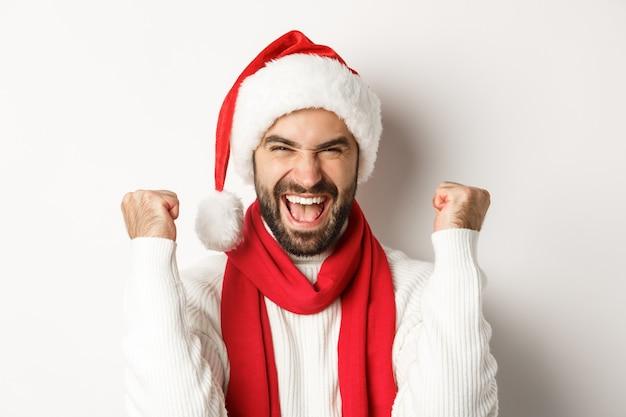 Concept de fête du nouvel an et de vacances d'hiver. gros plan d'un homme excité en bonnet de noel se réjouissant, gagnant ou célébrant en bonnet de noel, debout sur fond blanc