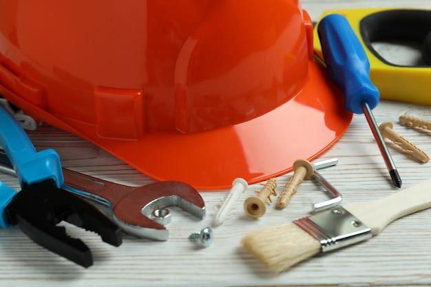 Concept de la fête du travail avec différents outils de construction sur fond de bois blanc