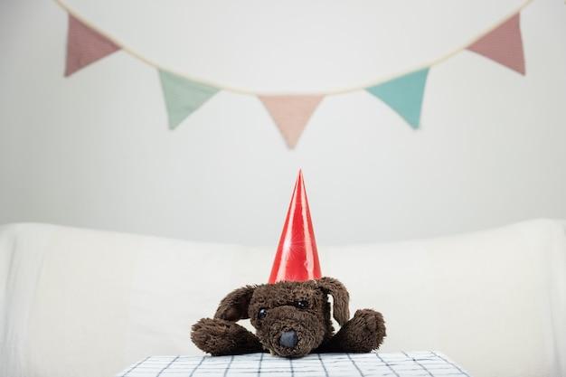 Concept de fête d'enfants avec chien jouet moelleux à la table. animal en peluche dans un fond festif minimaliste à l'intérieur