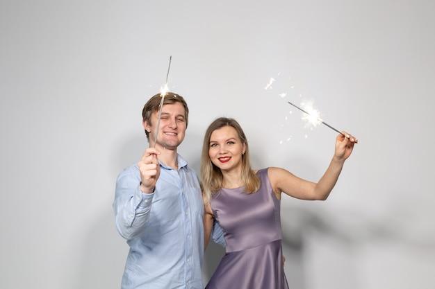 Concept de fête, famille, nouvel an, noël et vacances - jeune couple à la recherche de cierges magiques sur fond blanc