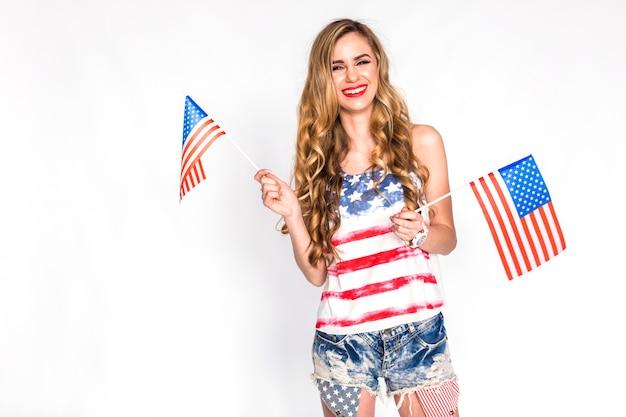 Concept de fête de l'indépendance des états-unis avec femme tenant des petits drapeaux américains