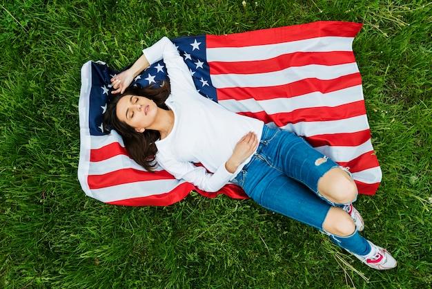 Concept de fête de l'indépendance avec une femme allongée sur le drapeau américain