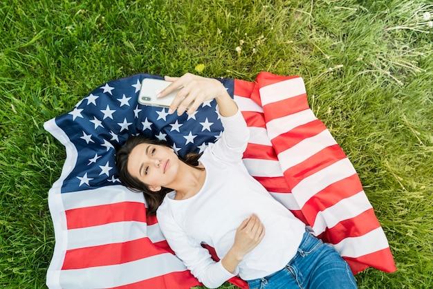 Concept de fête de l'indépendance avec femme prenant selfie sur le drapeau américain