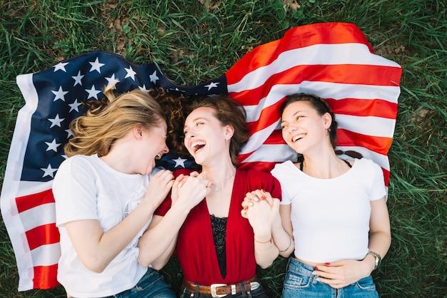 Concept de la fête de l'indépendance avec des filles allongées sur le drapeau américain