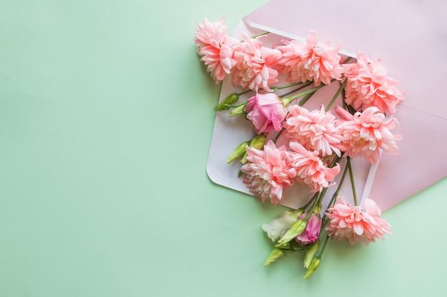 Concept de fête des mères. bouquet de lisianthus roses, chrysanthèmes avec enveloppe. note de papier vierge pour copyspace.card à l'occasion de la fête des mères, d'une invitation de mariage, d'un anniversaire ou d'un mot de remplissage