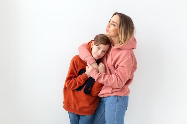 Concept de fête des mères, enfants et famille - garçon adolescent étreignant sa mère sur une surface blanche