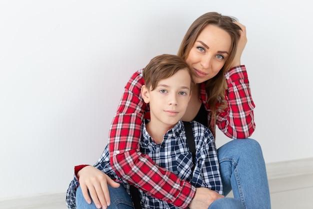 Concept de fête des mères, enfants et famille - mignon garçon adolescent avec sa jeune mère à la maison