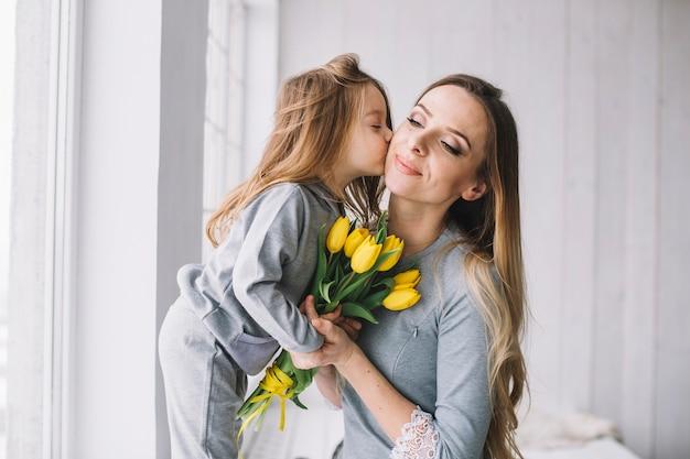 Concept de fête des mères avec la fille embrasse la mère