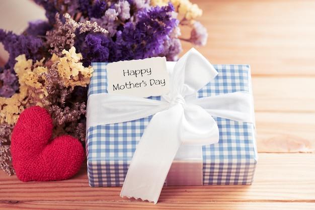 Concept de fête des mères heureux. boîte-cadeau avec fleur, étiquette en papier avec texte de la fête des mères amour