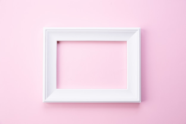 Concept de fête des mères heureux. vue de dessus du cadre photo blanc sur fond rose