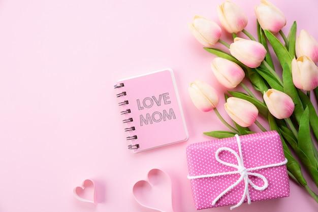 Concept de fête des mères heureux. vue de dessus des fleurs de tulipes roses, boîte-cadeau