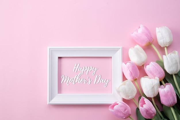 Concept de fête des mères heureux. vue de dessus des fleurs de tulipes roses et cadre photo blanc