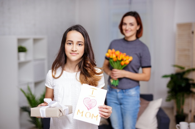 Concept de fête des mères - jolie fille faisant une surprise à la mère avec une boîte-cadeau et une carte de voeux faite à la main