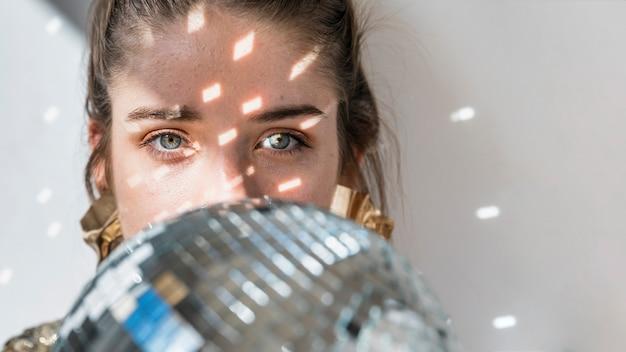 Concept de fête de nouvel an avec une fille derrière une boule disco