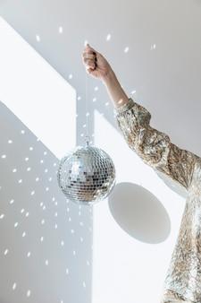 Concept de fête de nouvel an avec fille tenant une boule disco