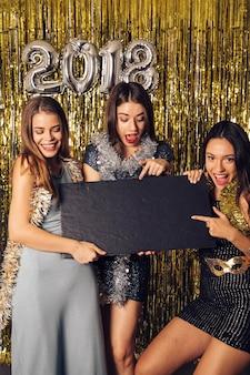 Concept de fête de nouvel an avec des filles pointant au conseil