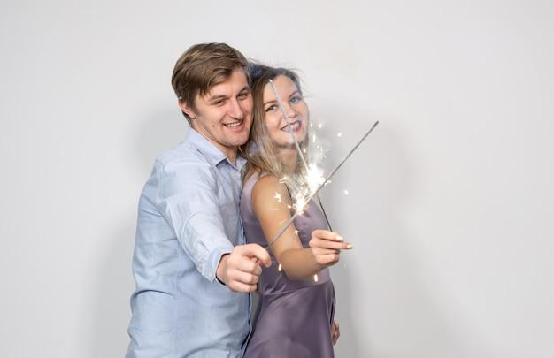 Concept de fête, nouvel an, noël et vacances - jeune couple célébrant son anniversaire avec des cierges magiques sur fond blanc