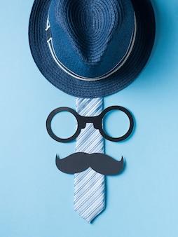 Concept de fête des pères avec chapeau, des lunettes et une cravate sur fond bleu