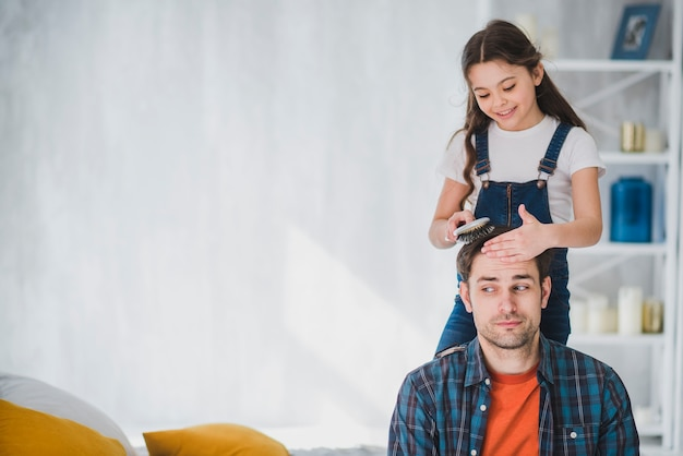 Concept de fête des pères avec la fille coupe les cheveux des pères