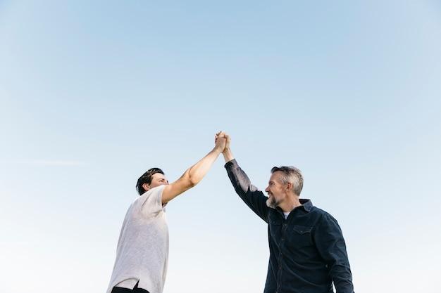 Concept de fête des pères avec fils et père se serrant la main