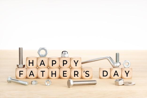 Concept de fête des pères heureux. blocs en bois avec texte sur table avec clé, écrous et vis. copiez l'espace.