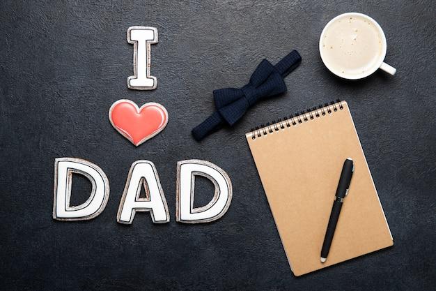 Concept de fête des pères heureux. cookies et bloc-notes et une tasse de café. place pour le texte