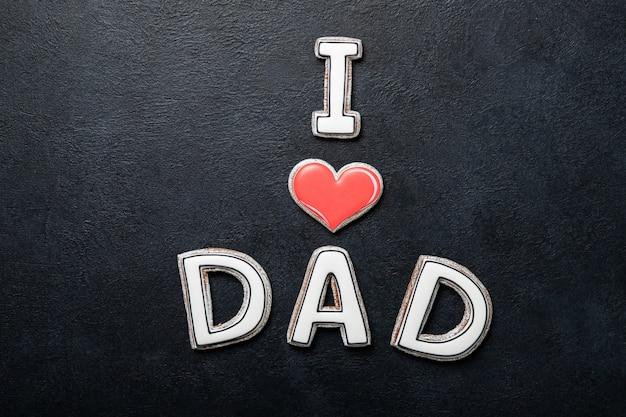 Concept de fête des pères heureux. cookies sur fond noir. texte j'aime papa.