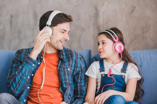 Concept de fête des pères avec père et fille écoutant de la musique