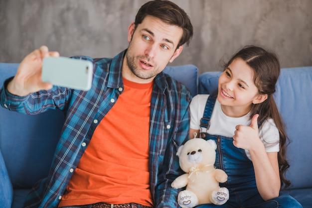 Concept de fête des pères avec père et fille prenant selfie