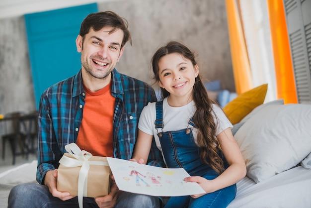 Concept de fête des pères avec père et fille tenant des cadeaux