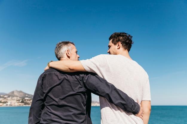 Concept de fête des pères avec père et fils en face de la mer