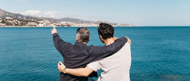 Concept de fête des pères avec père et fils, regardant vers la mer