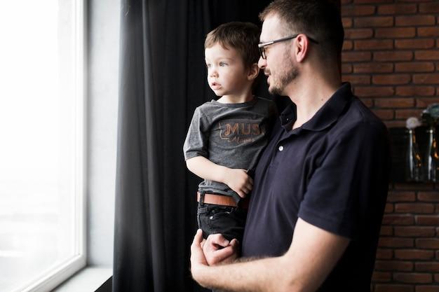 Concept de fête des pères avec père et fils regarde par la fenêtre