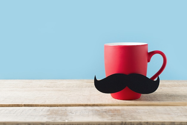 Concept de fête des pères avec une tasse rouge et moustache sur fond bleu