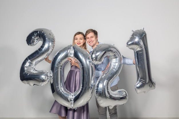 Concept de fête, de personnes et de vacances du nouvel an - femme et homme célébrant le nouvel an 2021