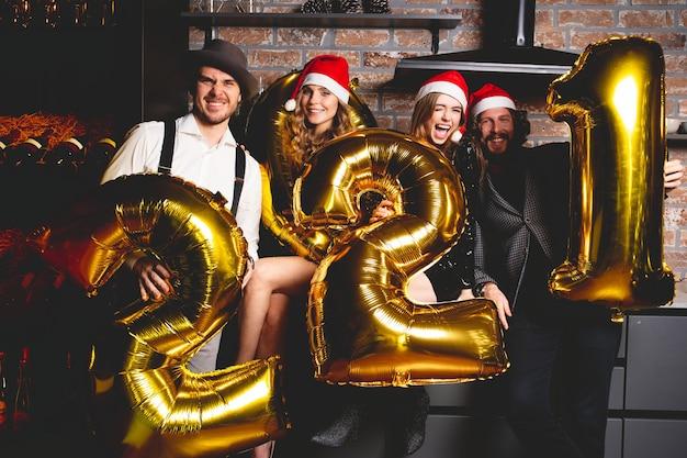 Concept de fête, de personnes et de vacances du nouvel an - femmes et hommes célébrant le nouvel an 2021.