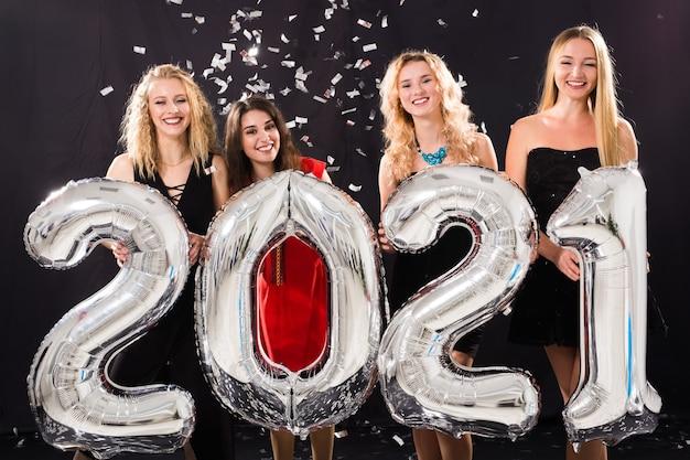 Concept de fête, de personnes et de vacances du nouvel an - joyeuses jeunes femmes célébrant le nouvel an 2021