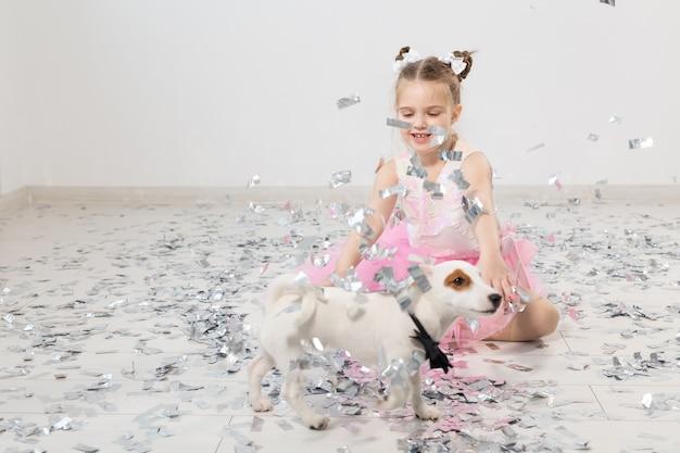 Concept de fête, vacances, anniversaire, nouvel an et célébration - enfant mignon avec des confettis et un chien