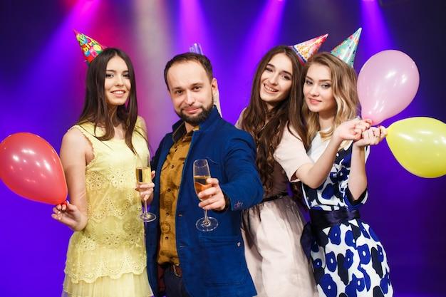 Concept de fête, vacances, célébration, vie nocturne et personnes - amis souriants avec des verres de champagne en club