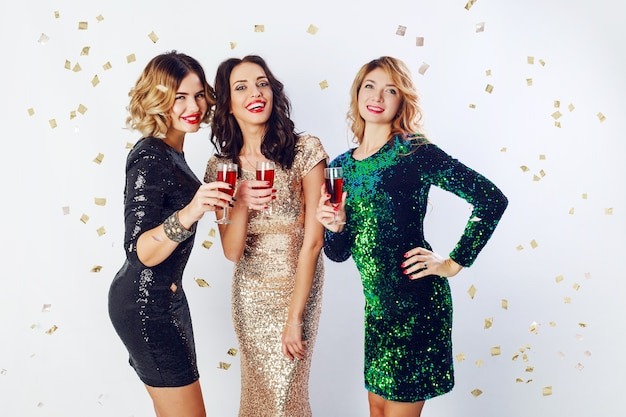 Concept de fête et de vacances. trois femmes glamour en robe de paillettes scintillantes de luxe buvant des cocktails et s'amusant