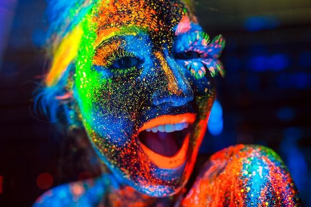 Concept. la fille sourit. portrait d'une fille peinte en poudre fluorescente.